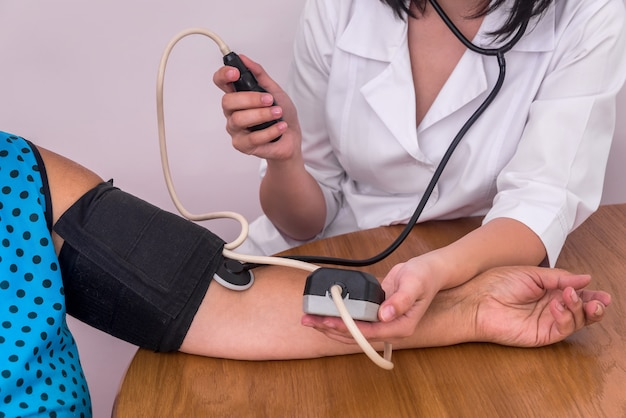 Mani di medici e pazienti con tonometro che misura la pressione sanguigna