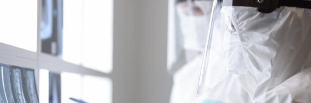 I medici in tute protettive stanno esaminando i raggi x in clinica