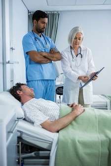 Medici che mostrano referto medico al paziente