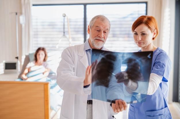 Medici in piedi nella stanza d'ospedale, esaminando i raggi x dei polmoni.