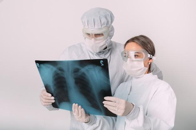 I medici in piedi su sfondo bianco esaminano i raggi x per la polmonite di un paziente covid-19 nella clinica. concetto di coronavirus.