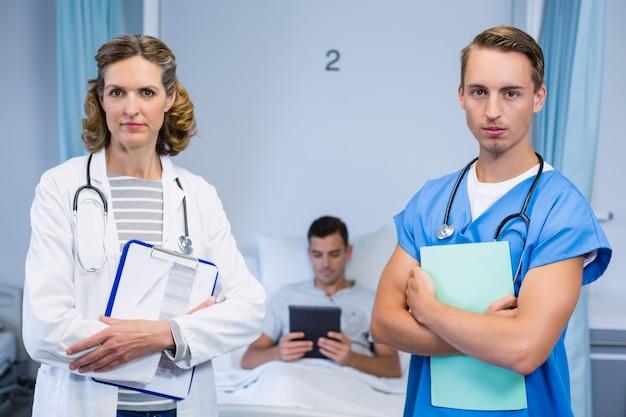 Medici in piedi con rapporti e paziente utilizzando la tavoletta digitale