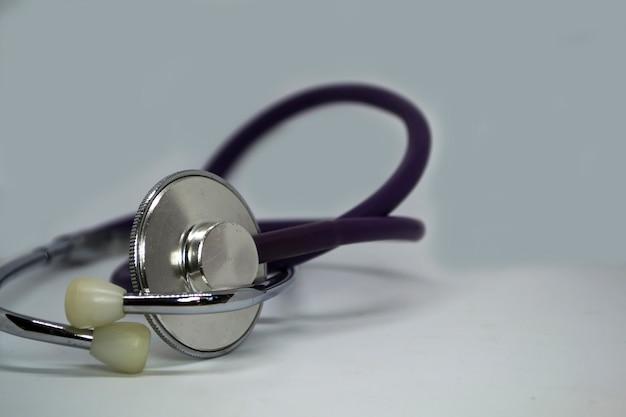 Uno stetoscopio di medici su un controllo cardiaco del fondo bianco