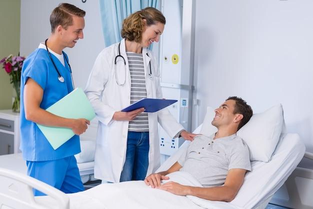 Medici che parlano con paziente nel letto di ospedale