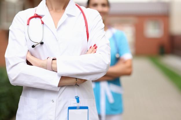 I medici veterinari stanno con sicurezza con le mani giunte sullo sfondo del medico di fattoria