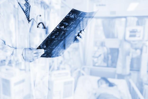 Medici guardando film x-ray del paziente con paziente offuscata in ospedale camera, concept medicine background