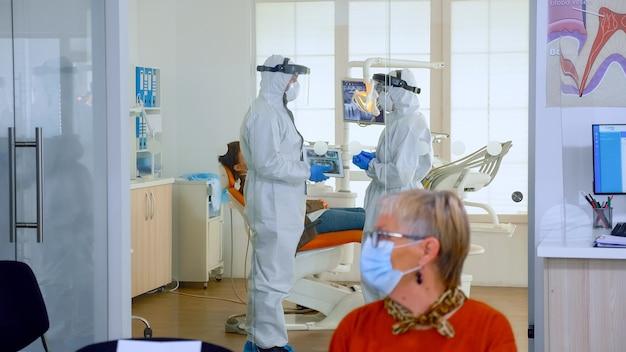 Medici che indossano un'uniforme di protezione antivirus completa in piedi nella sala operatoria che pianificano il trattamento dentale mentre i pazienti anziani aspettano alla reception mantenendo le distanze. concetto di nuova normale visita dal dentista