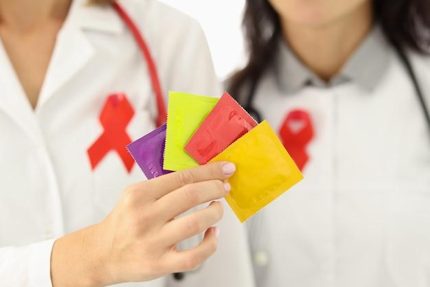 I medici in camice bianco tengono il pacchetto di preservativi nelle loro mani