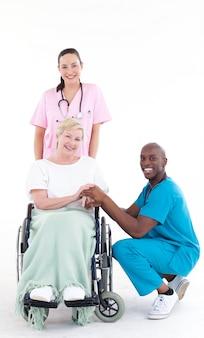 Medici con un paziente in una sedia a rotelle che sorride alla macchina fotografica