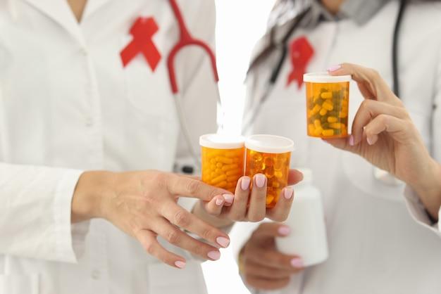 I medici con il nastro rosso sulle uniformi stanno tenendo i barattoli del primo piano dei farmaci