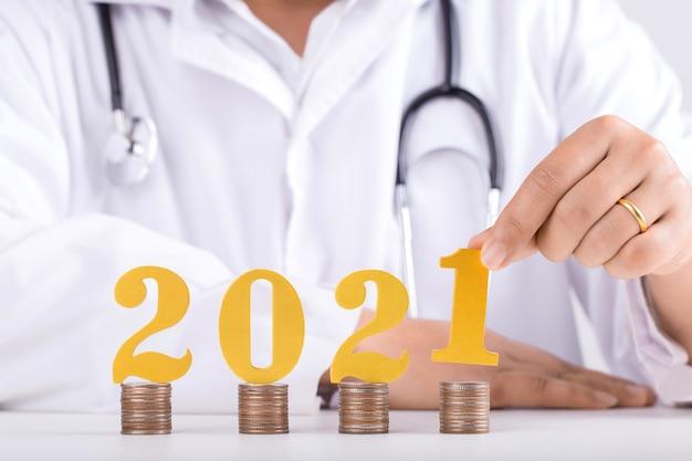 Mani di doctro che mettono il numero di legno dell'oro 2021 sulla pila di monete. 2021 risparmio di denaro per il nuovo anno e pianificazione finanziaria. anno nuovo e concetto di salute.