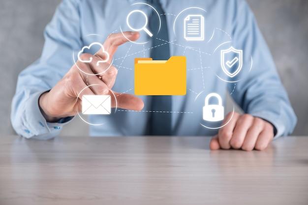 Sistema di gestione dei documenti dms. icona della cartella e del documento della tenuta dell'uomo d'affari. software per l'archiviazione, la ricerca e la gestione di file e informazioni aziendali. concetto di tecnologia internet. sicurezza digitale.