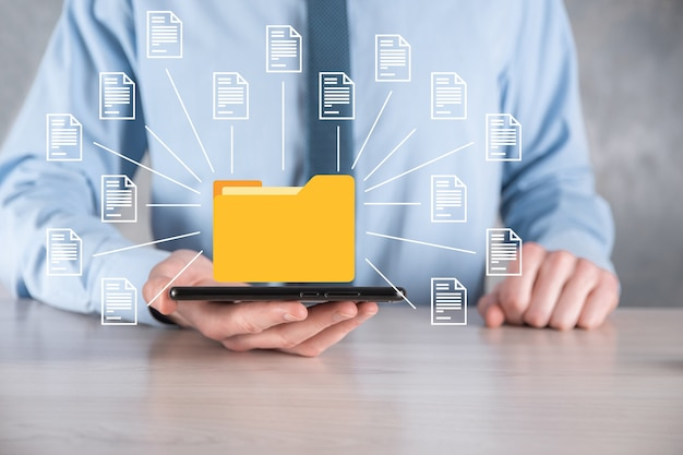 Document management system dms .businessman tenere cartella e icona documento.software per l'archiviazione
