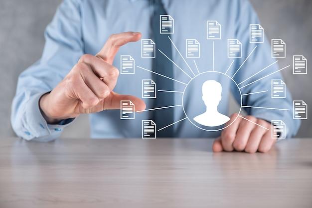 Sistema di gestione dei documenti dms. uomo d'affari trattiene l'icona dell'utente e del documento. software per l'archiviazione