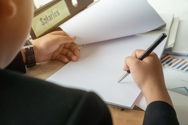 Rapporto sul documento o concetto di gestione aziendale: mani del manager dell'uomo d'affari che tengono la penna per leggere, firmare documenti vicino al raccoglitore dello stipendio del libro paga, rapporto riassuntivo affari delle risorse umane con grafico