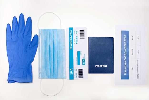 Documenti e oggetti per il viaggio aereo durante l'epidemia di covid-19: passaporto, biglietto, test pcr per covid-19, maschera facciale, guanti, primo piano.