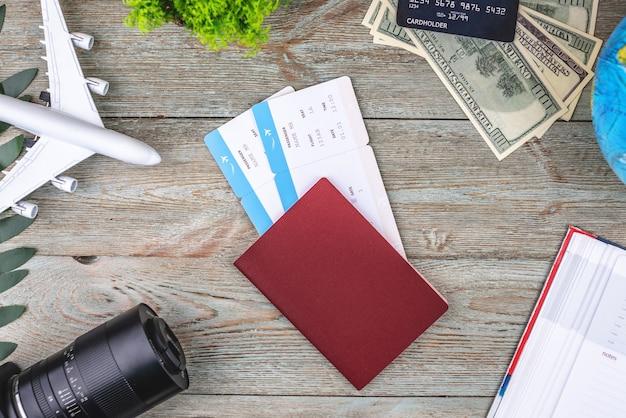 Documenti, biglietti aerei e altre forniture di viaggio su uno sfondo di legno