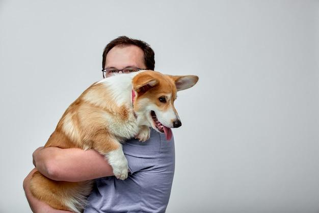 Il cane si trova sulla spalla del suo proprietario. il gallese corgi nelle mani del suo proprietario sul muro bianco. il concetto di persone e animali.