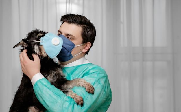 Cane in maschera protettiva, condizioni antigieniche, il medico tiene in mano un cane che è malato di coronavirus,
