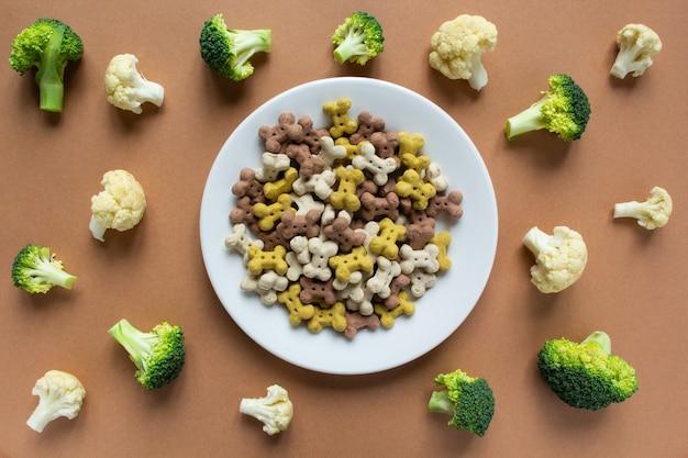 Croccantini secchi vegetariani per cani su piatto e verdure su superficie beige