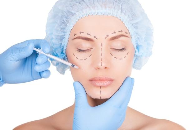 Facendo un'iniezione di botox. bella giovane donna senza camicia in copricapo medico e schizzi sul viso tenendo gli occhi chiusi mentre i medici fanno un'iniezione in faccia