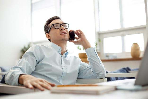 Facendo affari. bello determinato uomo dai capelli scuri dagli occhi scuri parlando al telefono e con gli occhiali mentre è seduto al tavolo