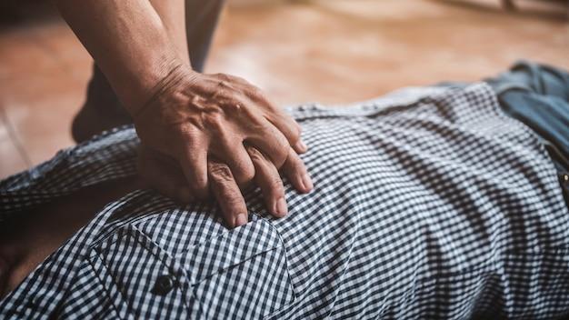 Fare il primo soccorso cpr all'uomo con attacco di cuore parte del processo di rianimazione, primo piano con stile vintage.