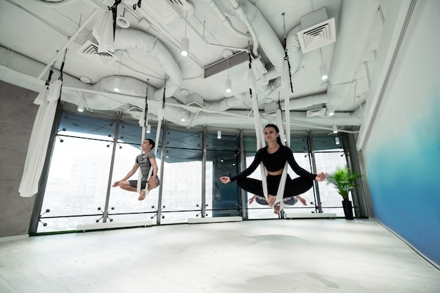 Fare yoga volante. donne e uomini che indossano abiti sportivi si sentono fantastici mentre fanno yoga in volo