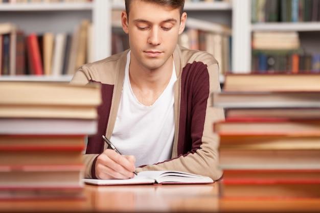 Facendo le sue ricerche in biblioteca. giovane fiducioso che scrive qualcosa nel suo taccuino mentre è seduto alla scrivania della biblioteca