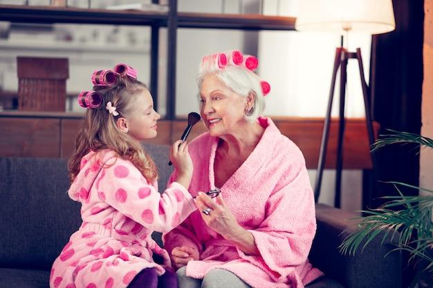 Truccarsi insieme. ragazza e nonna con bigodini e accappatoi rosa che si truccano insieme