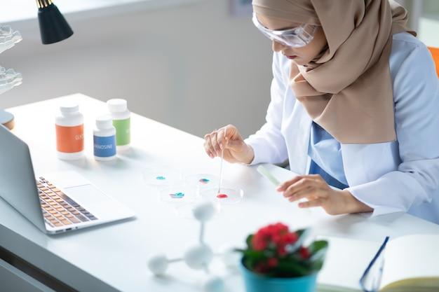 Facendo alcuni esperimenti. chimico femminile che indossa occhiali protettivi e foulard facendo alcuni esperimenti