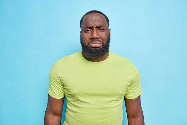 Dolente frustrato uomo adulto barbuto con la pelle scura sconvolto per qualcosa acciglia il viso sembra dispiaciuto sul davanti vestito con una maglietta verde casual isolata sul muro blu