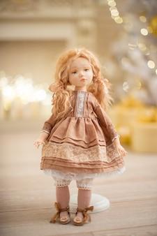 Bambola in abito vicino all'albero di natale