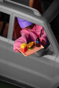La persona bambola prende un ordine di cibo spazzatura attraverso l'auto