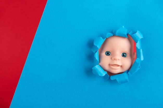 Il viso della bambola fa capolino da dietro pezzi di carta blu, primo piano. copia spazio.