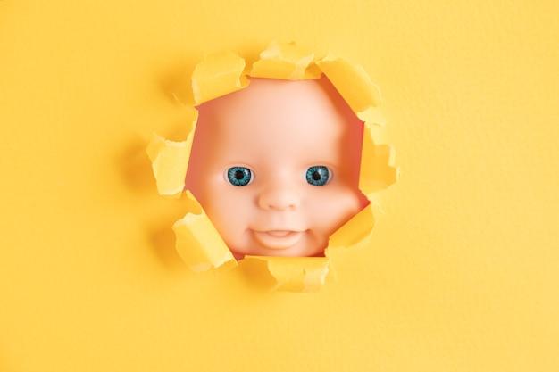 Il viso della bambola fa capolino da dietro pezzi di carta gialla, primo piano. copia spazio.