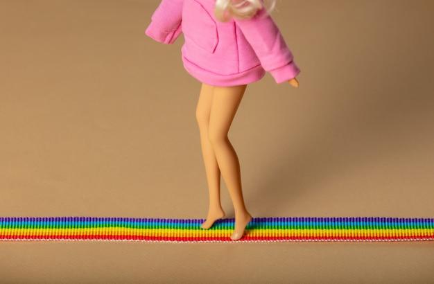 Bambola che cammina sulla striscia arcobaleno lgbt