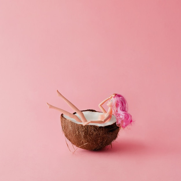 Bambola con i capelli rosa che fa il bagno nella noce di cocco