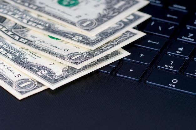 Banconote in dollari sulla tastiera del computer nero