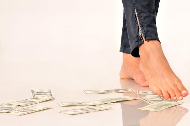Banconote in dollari sul pavimento sotto le gambe della donna per implicare la caduta o la svalutazione delle valute delle fatture del dollaro.
