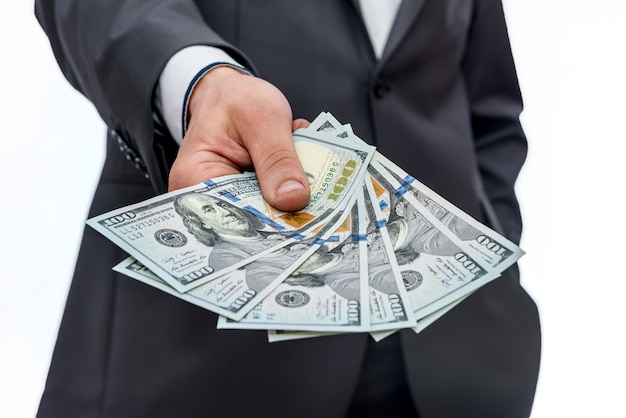 Le banconote del dollaro nelle mani maschii si chiudono su
