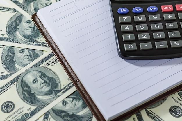 Banconote in dollari, blocco note aperto e calcolatrice. finanza, contabilità o concetto di risparmio.