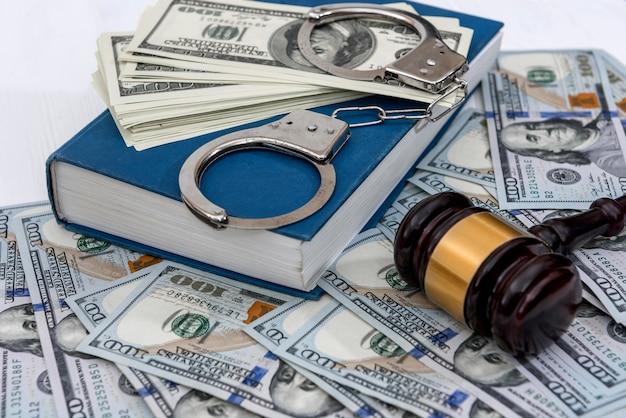 Banconote in dollari con manette sul libro blu