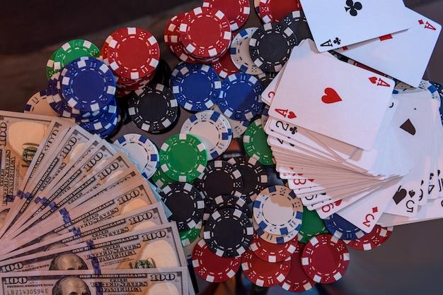 Banconote in dollari con fiches da poker e carte da gioco