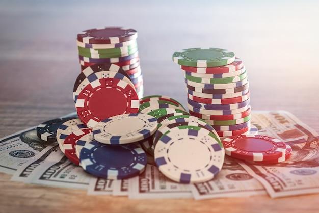 Banconote in dollari sul tavolo di legno con fiches del casinò