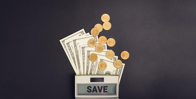 Banconote in dollari e monete del mucchio con la calcolatrice, concetto di crescita dei soldi e successo dell'obiettivo.