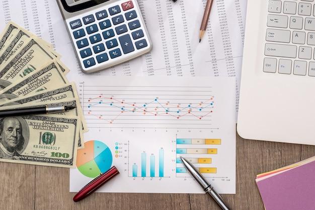 Fatture del dollaro su un tavolo con grafico grafico e laptop, penna e calcolatrice