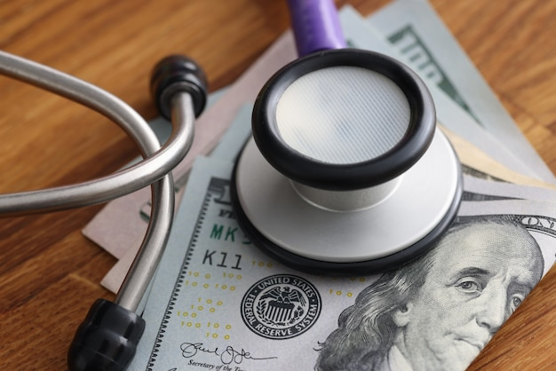Banconote in dollari sul tavolo con stetoscopio su di loro tangenti in strutture mediche concept facilities