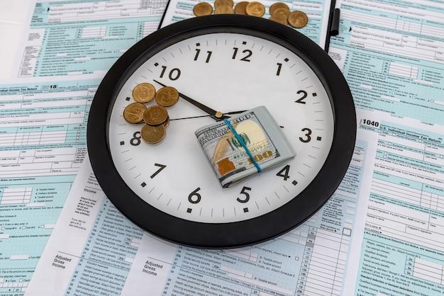 Monete e banconote del dollaro con l'orologio al modulo 1040