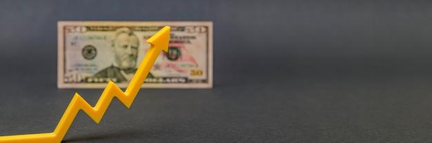 Inflazione del dollaro, deprezzamento del dollaro, calo del potere d'acquisto della valuta americana. copia spazio. banconota da cinquanta dollari su sfondo nero e freccia su.